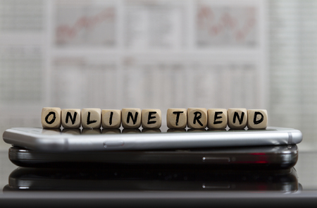 online trend letters on wooden cubes on mobile phones with blurred business newspaper in the background
