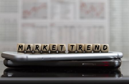 Market trend word on cell phones with blurred business newspaper background