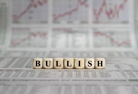 Bullish stock market on wooden cube on a business newspaper background