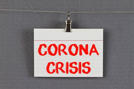 CORONA crisis written on a sticky note on a pin board Imagens
