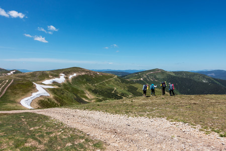 mountain landscape: Four tourists on the lookout in the spring beautiful mountains under a blue sky Svydovets Range Carpathians West Ukraine Stock Photo