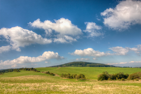czech: Beautiful summer countryside with grassfield under blue sky with clouds - Czech Republic, Europe Stock Photo