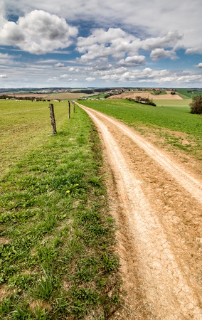 grassfield: Spring countryside with dirt road through green pastures and blue sky with white clouds - Czech Republic, Europe Stock Photo