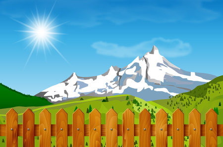 hilly: Wooden fence and mountain landscape in background. Mountainous landscape and wooden fence under blue sky with clouds and sun. Spring or summer season under mountains - wooden fence in foreground.