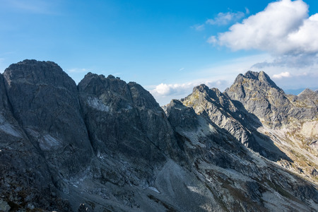 orla: Amazing rocky mountain ridge under blue sky with white clouds. Challenging mountain trail called Orla Perc. High Tatras National Park, Poland, Europe