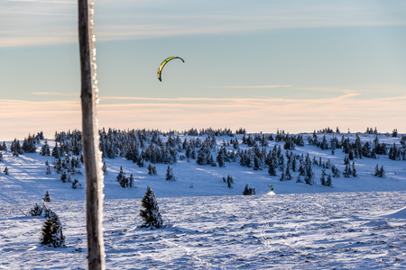 snowkiting: Snowkiter with kite on snowy field under blue sky