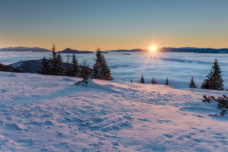 inversion: Amazing mountain sunrise above inversion low clouds. View from Little Fatra mountains ridge - West Tatras, Choc mountains and Low Tatras mountains on horizon. Slovakia, Europe. Stock Photo