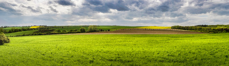 Panoramic view of spring landscape with green meadows and sky with dramatic clouds - Czech Republic, Europe