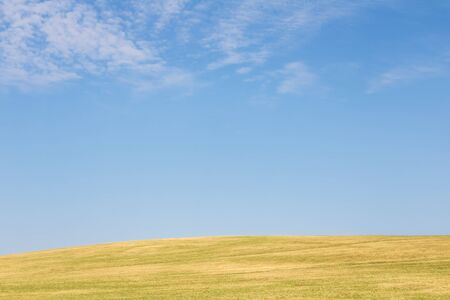 Spring or summer minimalist view of landscape with green meadow and blue sky with white clouds - Czech Republic, Europe