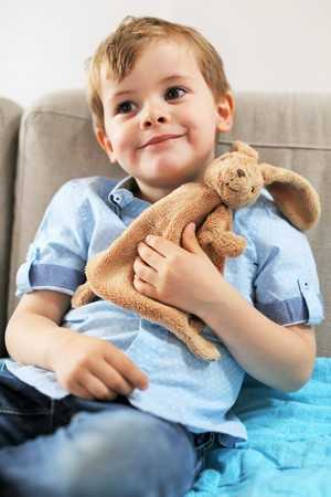 plush toy: A young toddler smilling with his plush toy Stock Photo