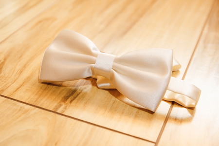 White mens wedding butterfly tie on the floor