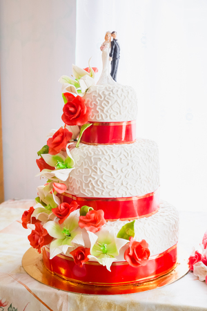 Red wedding cake decorated with red roses