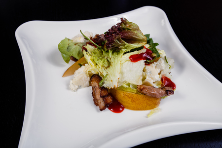 Appetizing salad sliced with pear slices of prosciutto pear arugula and parmesan on white plate