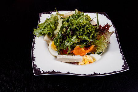 A colorful, tasty and healthy vegetable salat with red tomatoes, green cucumbers and pepper slices, white and yellow cheese, eggs and pesto sauce