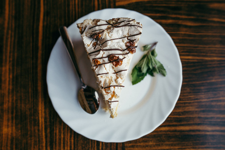 Slice of cake with chopped nuts on wooden chopping board