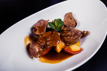 Duck liver with berry sauce and apples decorated with rosemary.