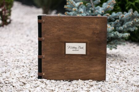 Photobook of wood. Wedding photo album with a wooden cover is on an unusual background with cones