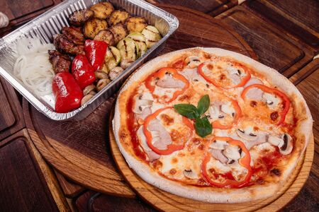 Roasted potatoes with grilled vegetables and meat on baking tray and pizza on wooden background as a studio shot