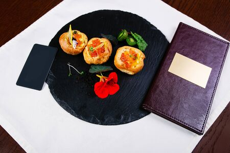 Smoked salmon canape sandwiches with salmon eggs or caviar on a black slate board with fresh parsley leaves, slices of lemon and capers. Overhead view