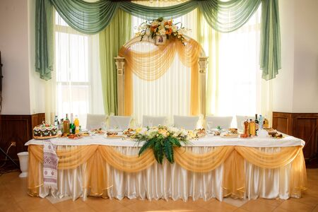 festive table for the bride and groom decorated with cloth and flowers in wedding day Standard-Bild