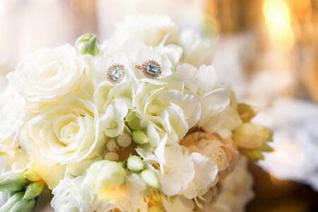 luxury pearl earings with stone on background of boutonnieres with roses
