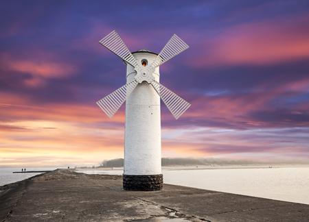 molino de agua: Faro molino de viento con el cielo espectacular puesta de sol, Swinoujscie, Mar Báltico, Polonia