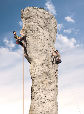 Climbers in action, young woman and man climbing difficult rock. photo