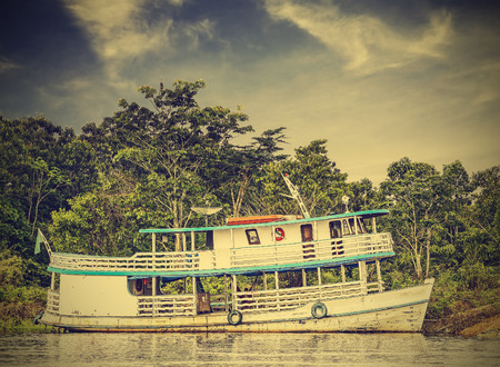 amazonas: Wooden boat on the Amazon river, Brazil, vintage retro  Stock Photo