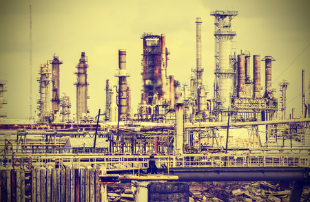 crude oil: Old industrial plant with gray sky, vintage retro style  Stock Photo