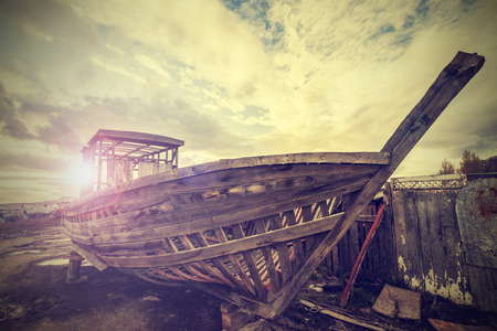discarded: Vintage Old Boat on Junk Yard  Stock Photo