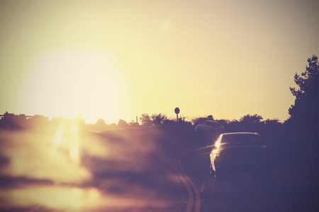 Vintage picture of road with cars in motion against sun  Stock Photo