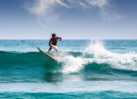 Mirissa, Sri Lanka - March 04, 2009 Silhouette of a surfer on waves on famous beach in Sri Lanka