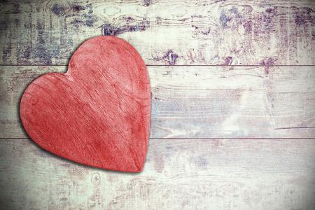 carta de amor: Coraz�n de madera rojo sobre fondo entramado de madera, espacio para el texto. Foto de archivo