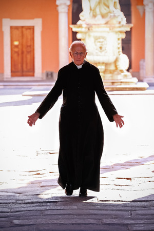 churchyard: Pisa, Italy - September 12, 2009: Priest walking on the churchyard in the old town of Pisa.