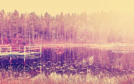 filtered: Vintage imagen filtrada del muelle del lago de madera en la puesta del sol.