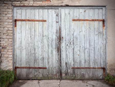 dowdy: Old wooden neglected garage door.