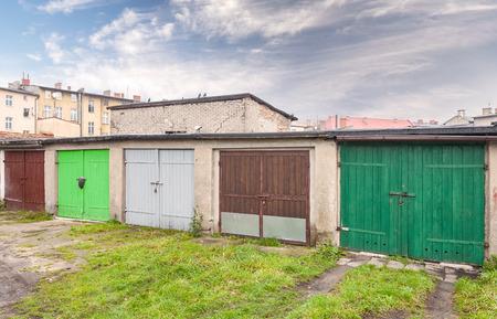 krottenwijk: Rij van garagedeuren in sloppenwijk.