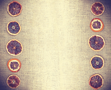 dried orange: Vintage natural background, dried orange on jute fabric.
