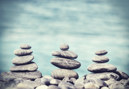 Vintage retro hipster style image of stones on beach, Zen spa concept background. Imagens