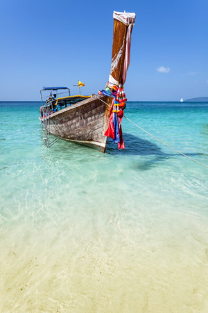 pristine corals: Wooden boat on crystal clear shallow water, Railay Beach.