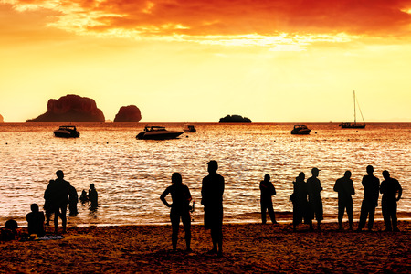 unknown: Silhouettes of unknown people watching red sunset.