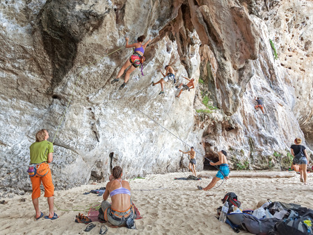 Railay, Thailand - December 31, 2014: Rock climbers climbing the wall on Railay beach, one of the most popular rock climbing locations in Asia.