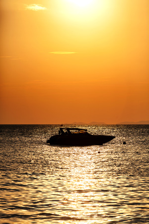 speed boat: Silhouette of a motor speed boat at sunset.