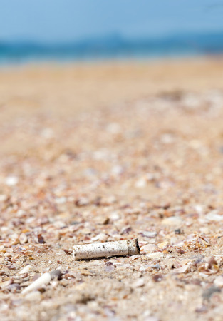 discard: Cigarette butt discarded left on beach, concept photo. Stock Photo