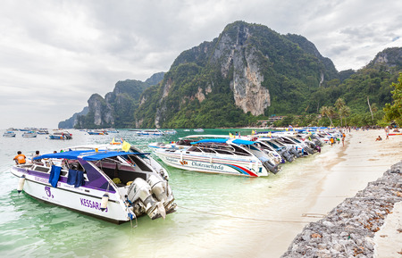 Phi Phi Island, Thailand - January 6, 2015: Speed boats and drivers waiting for tourists on the beach. Phi Phi is one of the most visited island in Thailand.