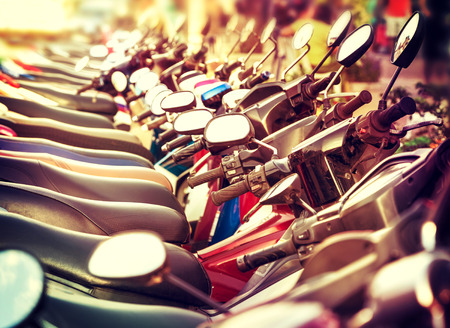 Retro filtered picture of scooter in a row. Stock Photo