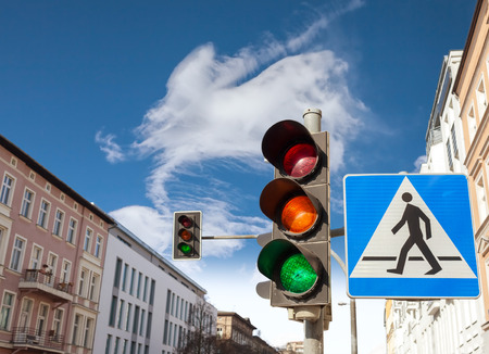 red  green: Traffic lights and pedestrian crossing sign in a city.