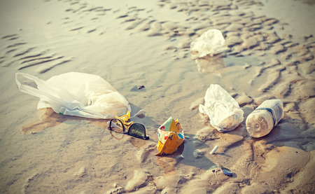 Garbage on a beach left by tourists, environmental pollution concept picture. Stock Photo