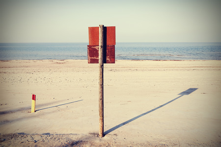 wooden post: Retro filtered rusty board sign on wooden post on a beach.