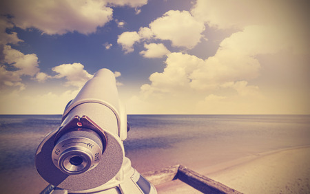 telescope: Retro toned picture of telescope on a beach pointed at beautiful sky.